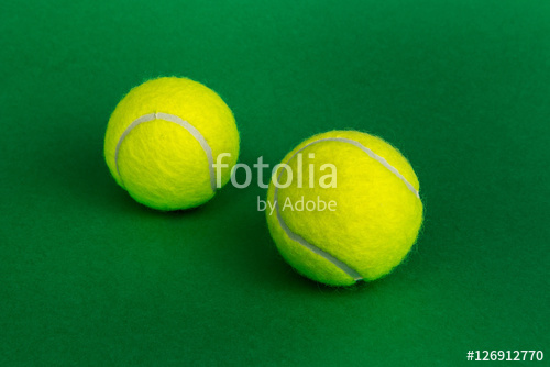 two tennis balls on a green background